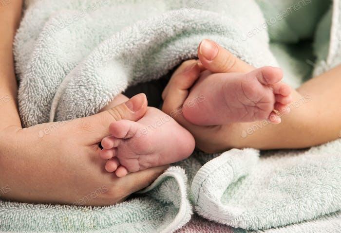 Мать держит ноги новорожденного