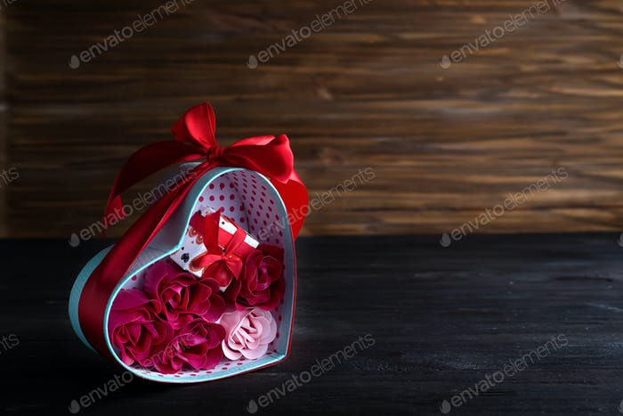 Valentines background with bouquet rose in gift box and mini gift box on dark wooden background