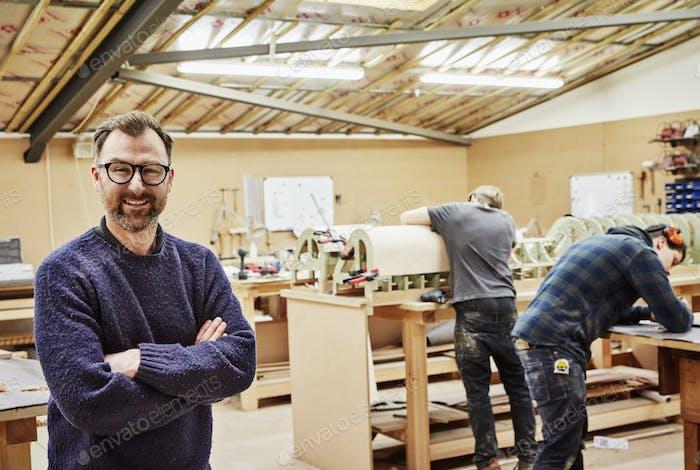 Tres personas en un taller de muebles haciendo piezas de muebles contemporáneos a medida.