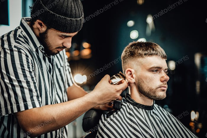Guy gets a haircut in modern and luxurious barbershop