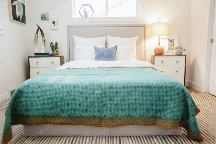 A bedroom with double bed and patterned quilt