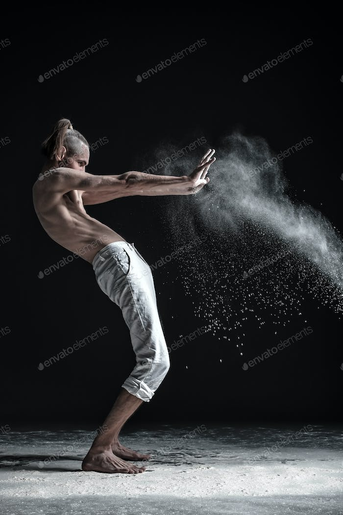 Portrait of caucasian young man wearing white sport pants doing yoga or pilates exercise.