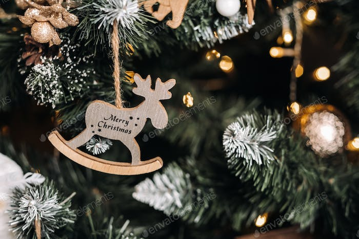 Christmas tree close-up with a hanging deer and the inscription merry Christmas