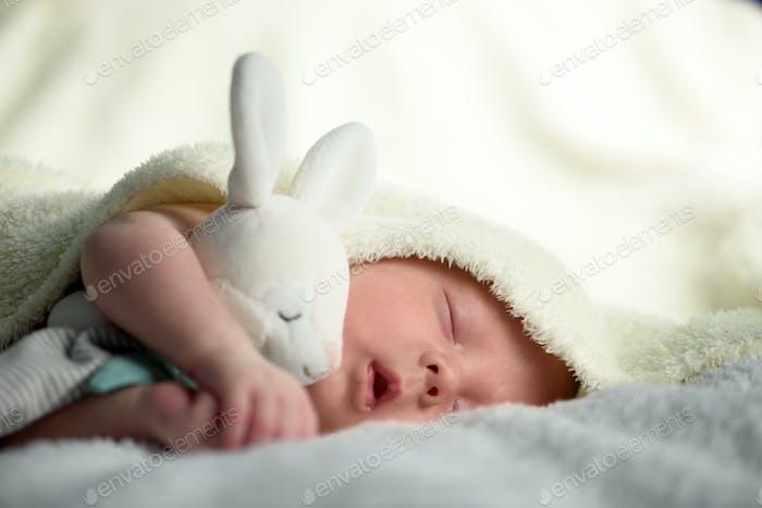 Newborn baby boy on white carpet closeup