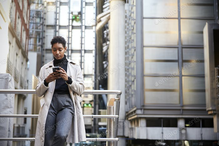 Fashionable young black woman standing using her smartphone