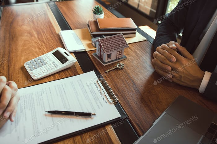 House sales representative sat at the office with the new home buyer.