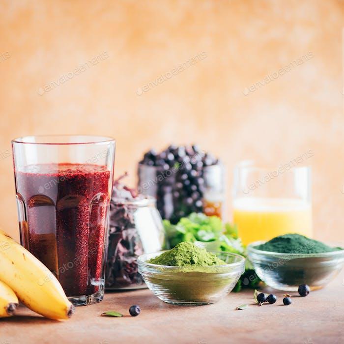 Fresh blueberries, bilberry, barley grass, spirulina powder, orange juice, dulse, cilantro on marble