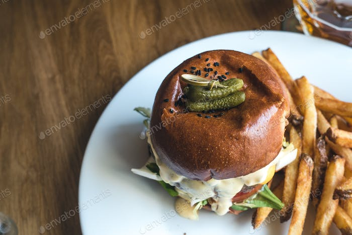 Tiny pickles on top of a mouthwatering beef burger with french fries