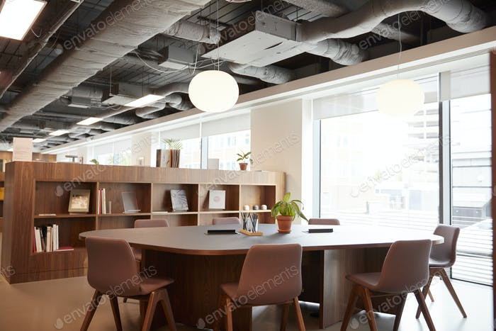 Chairs Around Table In Empty Modern Meeting Area Of Office