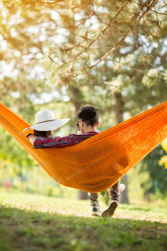 Guy with girlfriend in hammock from behind