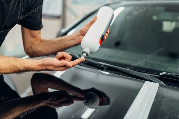 Male person with car polishing paste, carwash