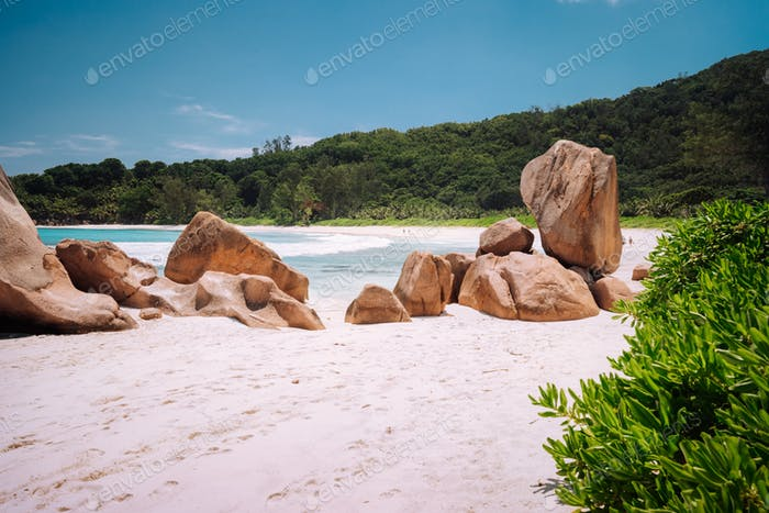 Beautifully shaped granite boulders in the turquoise ocean lagoon and a perfect white sand at Anse