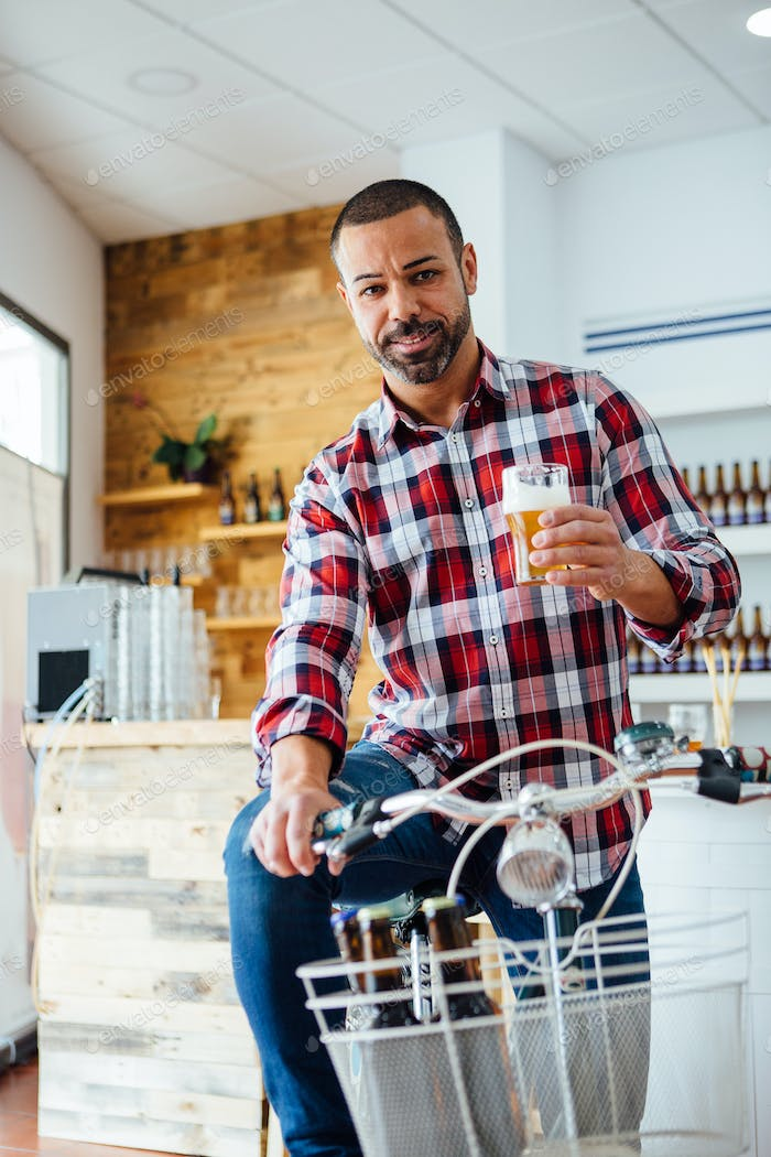 Portrait of man with beer on bike