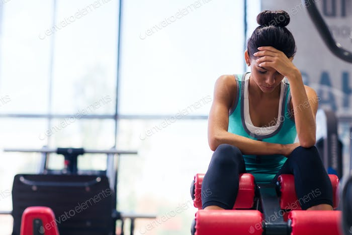 Tired woman sitting on exercises machine