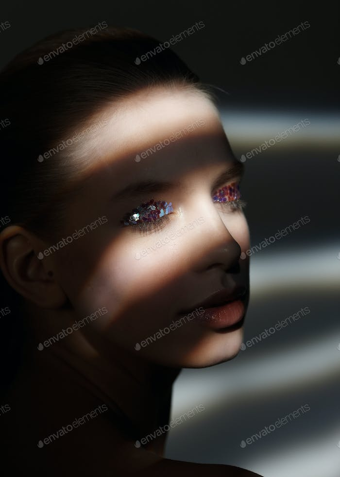 Portrait of woman with stripes of light on her face.