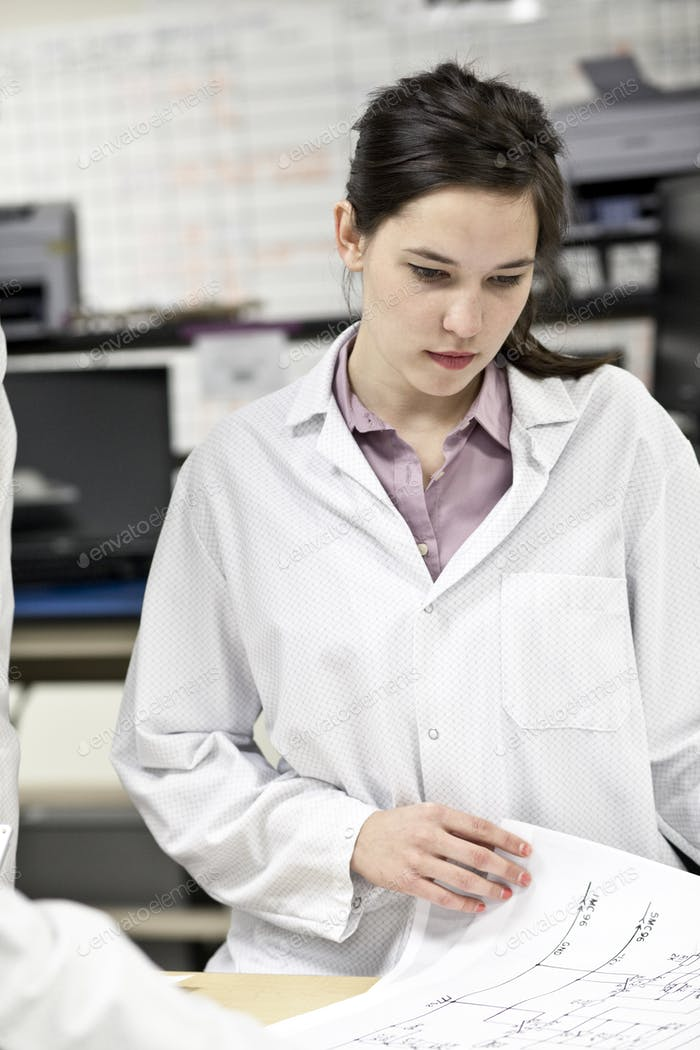 A caucaasian female techinician working over a problem in a technical research and development site.