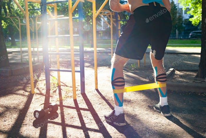 Entrenamiento irreconocible de atleta masculino usando banda de resistencia al aire libre