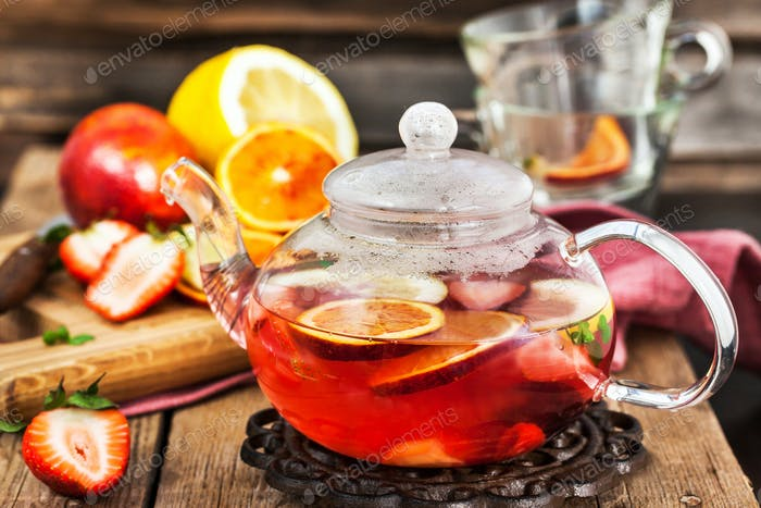 Fruit red tea with oranges and berries on wooden table