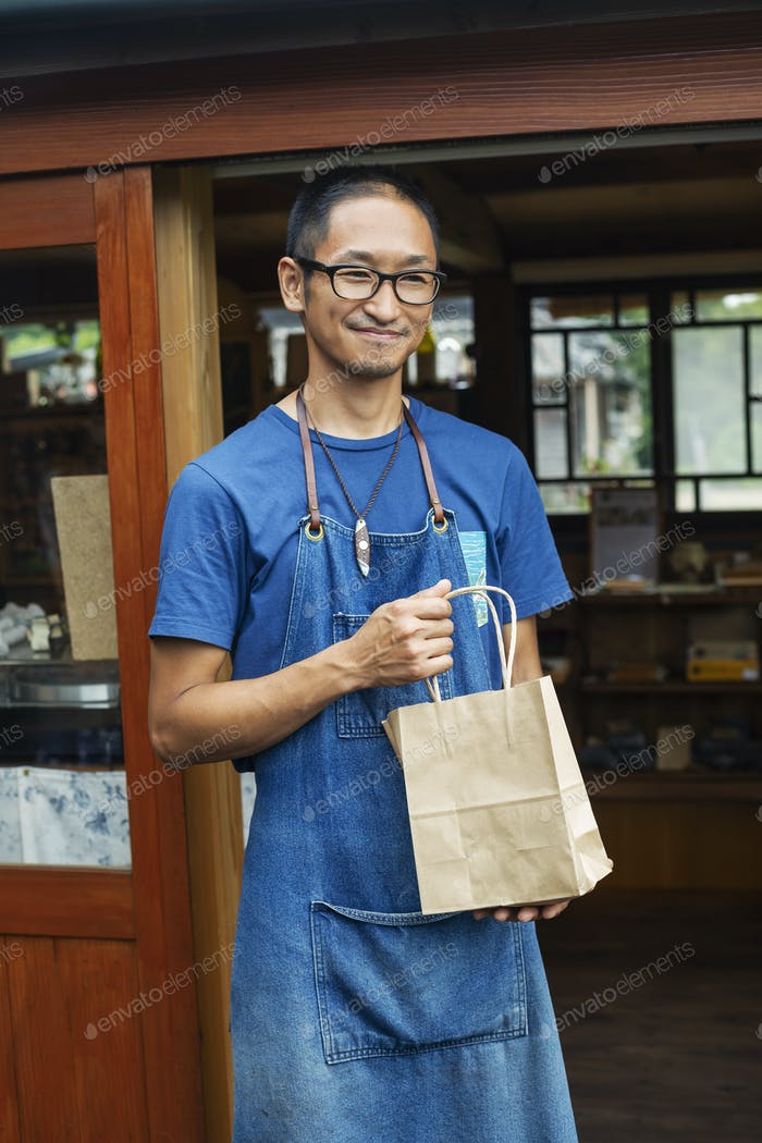 Japanese man wearing blue apron and glasses standing outside a leather shop, holding shopping bag,