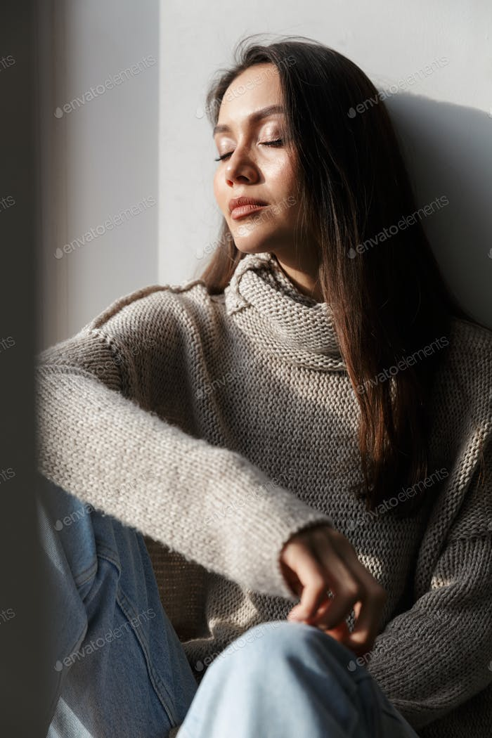 Image of relaxed asian woman sitting on window sill