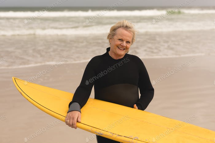 front view of an active senior woman standing with surfboard on the beach