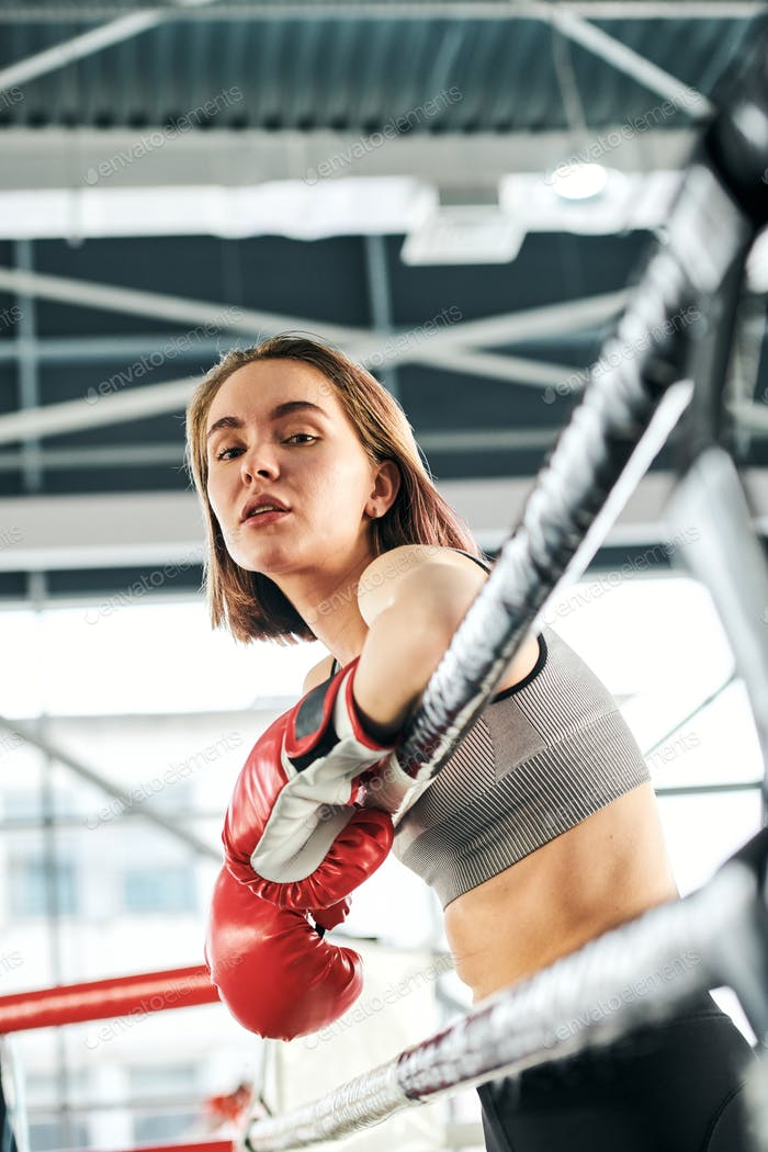 Pretty young confident female in activewear and boxing gloves standing by bars