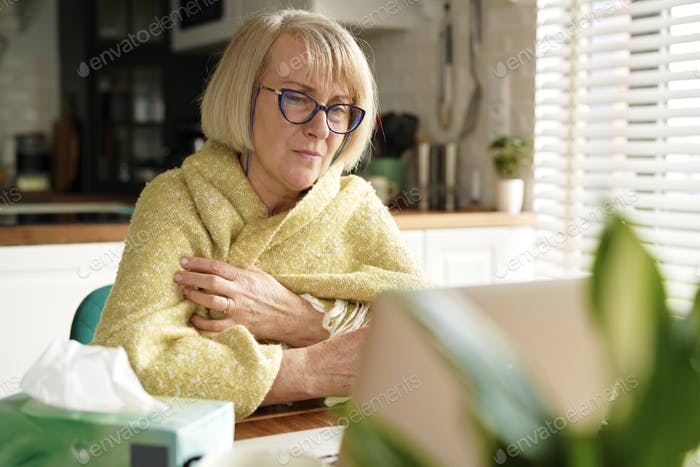 Senior woman sick at home in the kitchen