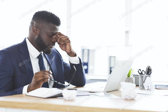 Tired african american businessman taking his glasses off