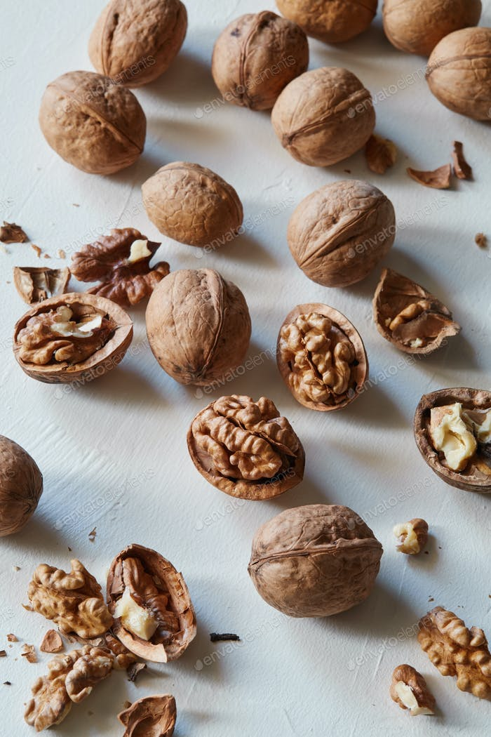 Walnuts and kernels on a white rustic backdrop