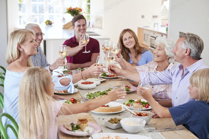 Group Of Multi-Generation Family And Friends Sitting Around Table And Making A Toast