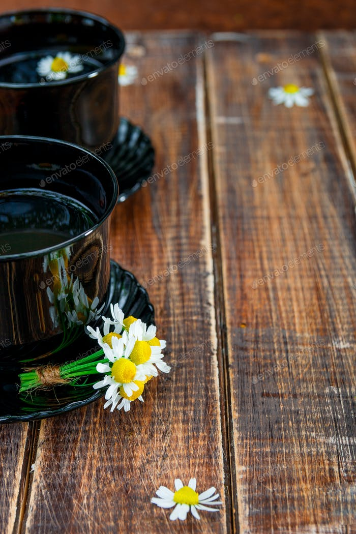Two black cup of tea with chamomile on wooden