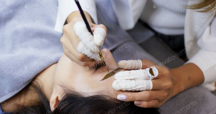 Asian woman gets facial beauty procedure, microblading procedure