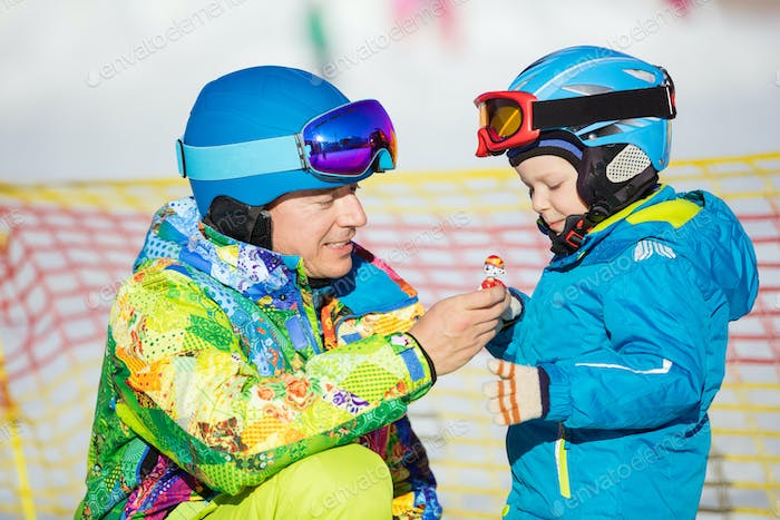 Father and little son in skiing outfits playing with toy