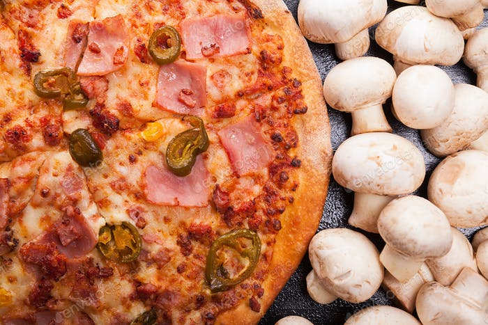 Top view of hot pizza next to mushrooms