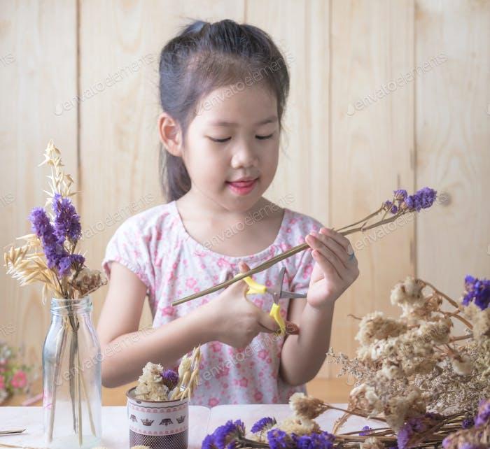 Girl trims the flower stem.