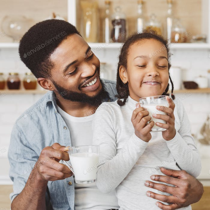 Little black girl enjoying her milk, spending time with father