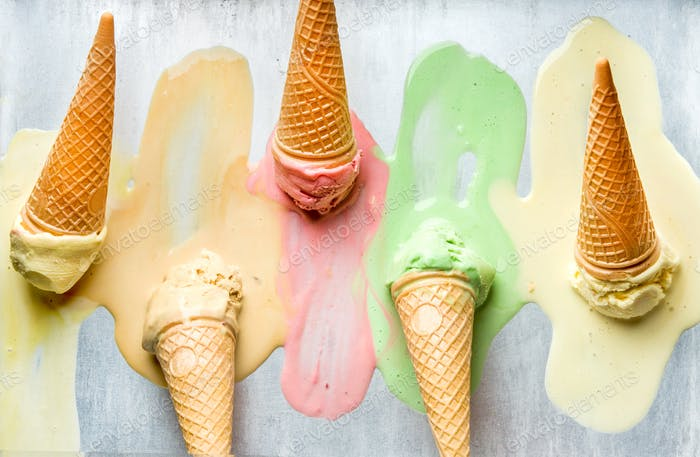 Colorful ice cream cones of different flavors. Melting scoops. Top view,  steel metal background.