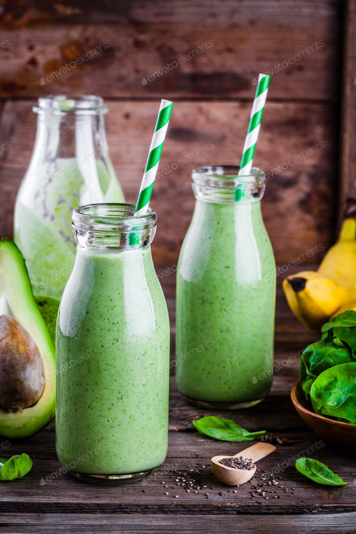 healthy green smoothie with banana, spinach, avocado  and chia seeds in glass bottles