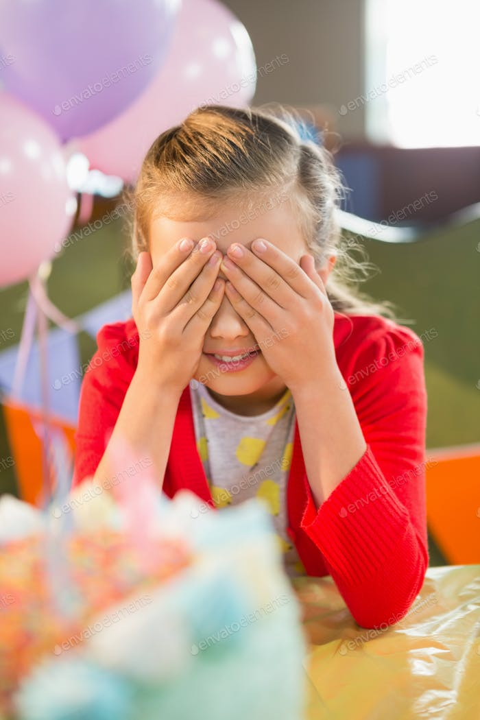 Cute girl covering her eyes during birthday party