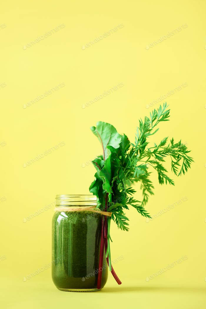 Organic smoothie with beet greens and carrot tops on yellow background, copy space. Summer vegan