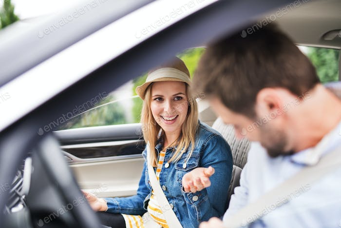 Happy young couple sitting in car, talking