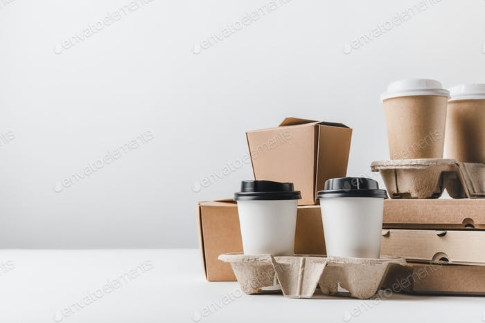 pizza boxes and coffee to go with noodles boxes on tabletop