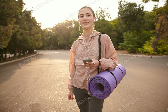 Horizontal photo of young nice woman walking after yoga at the park