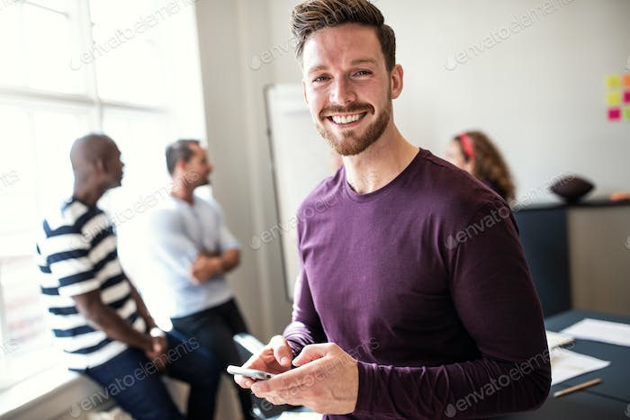 Smiling young designer using his cellphone after an office meeting