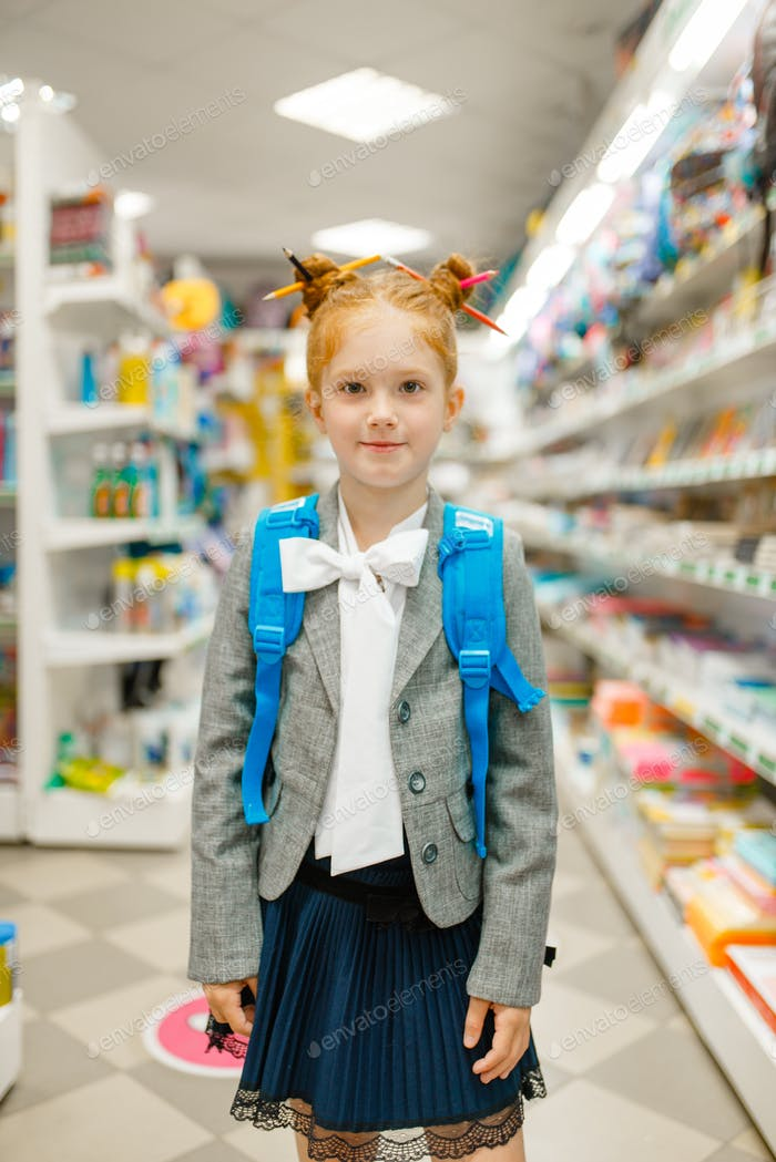 School girl with backpack in stationery store