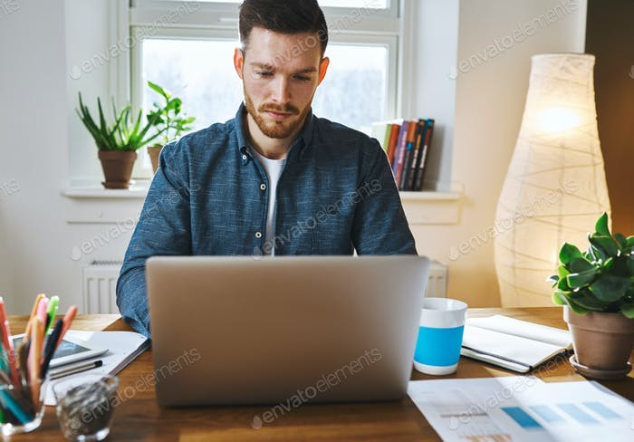 Serious man working on laptop