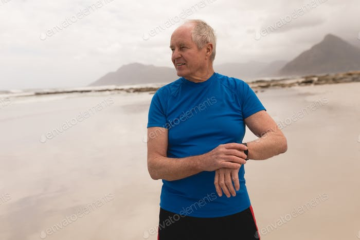 Happy senior man using smartwatch at the beach with moutains in the backgroun