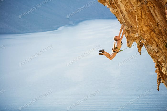Female rock climber jumping on handholds on challenging route