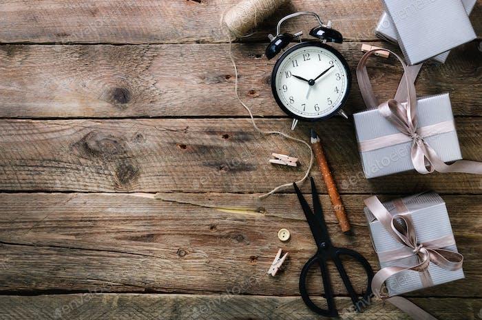 Geschenkboxen, schwarzer Wecker, Stift, Schere auf Holzhintergrund. Vorbereitung auf Geburtstag, Weihnachten