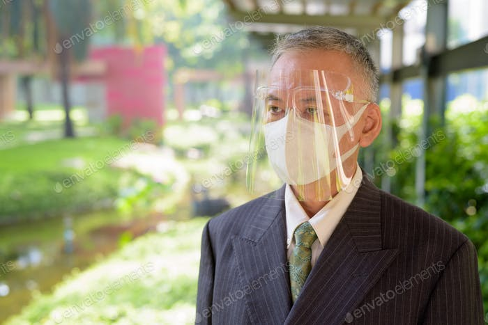 Mature Japanese businessman with mask and face shield thinking at the park